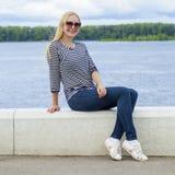 Junge Schönheit in den Blue Jeans, die in der Sommerstraßengleichheit sitzen Lizenzfreie Stockfotografie