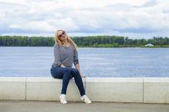 Junge Schönheit in den Blue Jeans, die in der Sommerstraßengleichheit sitzen Lizenzfreies Stockbild