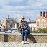 Junge Schönheit in den Blue Jeans, die in der Sommerstraßengleichheit sitzen Stockfoto