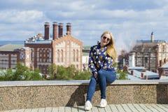Junge Schönheit in den Blue Jeans, die in der Sommerstraßengleichheit sitzen Stockfotos