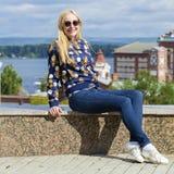 Junge Schönheit in den Blue Jeans, die in der Sommerstraßengleichheit sitzen Lizenzfreies Stockfoto