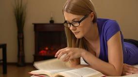 Junge Schönheit in den Gläsern, die auf einem Sofa, ein Buch lesend liegen 00347 stock footage