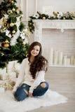Junge Schönheit in der Strickjacke und in Blue Jeans, die auf Boden nahe Weihnachtsbaum sitzen Lizenzfreies Stockbild