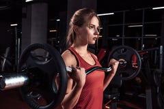 Junge Schönheit, die Übung mit Stange in einer Turnhalle tut Athletisches Mädchen, das Training in einer Eignungsmitte tut lizenzfreie stockfotos