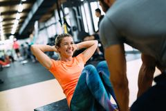 Junge Schönheit, die Übungen mit persönlichem Trainer tut lizenzfreie stockfotos