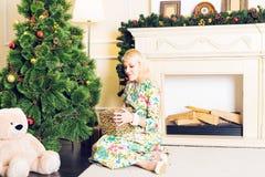 Junge Schönheit, die auf Boden nahe Weihnachtsbaum und Geschenken auf Sylvesterabend sitzt Innenraum mit Weihnachten Lizenzfreie Stockbilder