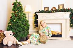 Junge Schönheit, die auf Boden nahe Weihnachtsbaum und Geschenken auf Sylvesterabend sitzt Innenraum mit Weihnachten Stockfotografie