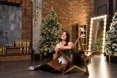 Junge Schönheit, die auf Boden nahe Weihnachtsbaum und Geschenken sitzt Stockfoto