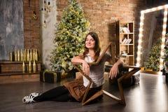 Junge Schönheit, die auf Boden nahe Weihnachtsbaum und Geschenken sitzt Lizenzfreie Stockbilder