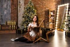 Junge Schönheit, die auf Boden nahe Weihnachtsbaum und Geschenken sitzt Stockfotos
