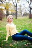 Junge Schönheit, die auf dem Grasschauen sitzt Stockbild