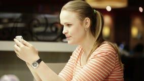 Junge Schönheit, die auf dem Smartphone sitzt im Café plaudert stock footage