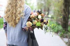 Junge Schönheit, die auf die Straße mit Tasche und Blumenstrauß geht Stockfotografie