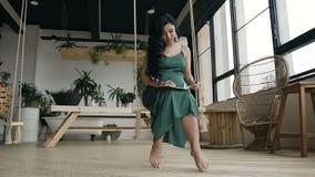 Junge Schönheit, die auf einem Schwingen sitzt und Aufnahmen in ihrem Notizbuch macht stock video footage