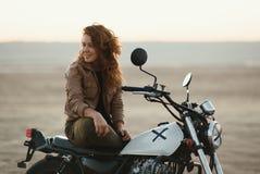 junge Schönheit, die auf ihrem alten Caférennläufermotorrad in der Wüste bei Sonnenuntergang oder Sonnenaufgang sitzt lizenzfreie stockbilder