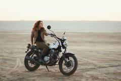 junge Schönheit, die auf ihrem alten Caférennläufermotorrad in der Wüste bei Sonnenuntergang oder Sonnenaufgang sitzt stockfotos