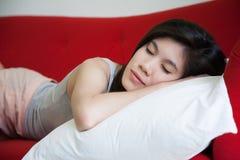 Junge Schönheit, die auf rotem Sofa schläft lizenzfreie stockbilder
