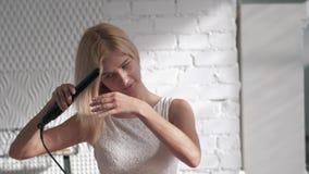 Junge Schönheit, die blondes Haar mit Eisen geraderichtet und im Raum lächelt stock footage