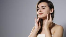 Junge Schönheit, die Creme auf ihrem Gesicht, lokalisiert auf Grau aufträgt stock footage