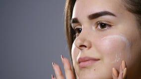 Junge Schönheit, die Creme auf ihrem Gesicht, lokalisiert auf Grau aufträgt stock video