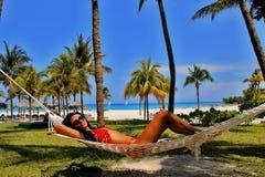 Junge Schönheit, die in der Hängematte auf dem tropischen Strand sich entspannt Lizenzfreie Stockfotos