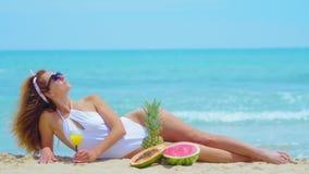 Junge Schönheit, die durch das Meer auf dem Sand mit orange frischem Saft liegt Konzeptferien stock footage
