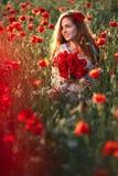 Junge Schönheit, die durch ein Mohnblumenfeld bei Sonnenuntergang geht und tanzt lizenzfreies stockbild
