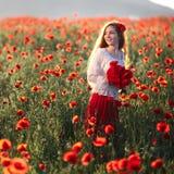 Junge Schönheit, die durch ein Mohnblumenfeld bei Sonnenuntergang geht und tanzt stockfotos