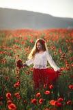 Junge Schönheit, die durch ein Mohnblumenfeld bei Sonnenuntergang geht und tanzt stockfoto