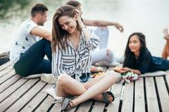 Junge Schönheit, die durch Fluss in der Firma von Freunden sich entspannt lizenzfreie stockbilder