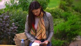 Junge Schönheit, die ein Buch sitzt auf einer Bank draußen in einem Park im Sommer liest 4 K stock video footage