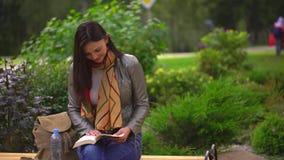 Junge Schönheit, die ein Buch sitzt auf einer Bank draußen in einem Park im Sommer liest 4 K stock video