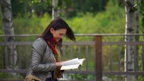 Junge Schönheit, die ein Buch sitzt auf einer Bank draußen in einem Park im Sommer liest 4 K stock footage