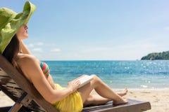 Junge Schönheit, die ein Buch am Strand an einem sonnigen Tag liest Stockfoto