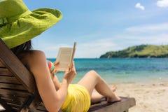 Junge Schönheit, die ein Buch am Strand an einem sonnigen Tag liest Lizenzfreies Stockbild
