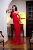 Junge Schönheit, die ein rotes Kleid im alten Weinlesehotel trägt Stockbild