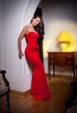 Junge Schönheit, die ein rotes Kleid im alten Weinlesehotel trägt Lizenzfreie Stockbilder