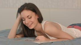 Junge Schönheit, die eine Zeitschrift im Bett liest stock footage