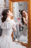 Junge Schönheit, die einen Spiegel untersucht Lizenzfreie Stockfotografie