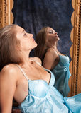 Junge Schönheit, die einen Spiegel untersucht Stockfotos