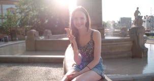 Junge Schönheit, die Eiscreme während des sonnigen Tages, draußen isst Stockfoto