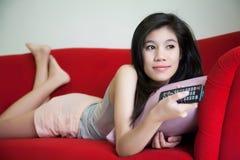 Junge Schönheit, die Fern-Fernsehen auf rotem Sofa hält lizenzfreie stockfotografie