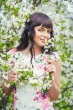 Junge Schönheit, die Geruch des blühenden Baums an einem sonnigen Tag genießt stockbilder