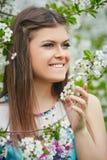 Junge Schönheit, die Geruch des blühenden Baums an einem sonnigen Tag genießt lizenzfreie stockfotos