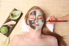 Junge Schönheit, die Gesichtsmassage und Badekur bekommt Stockbilder