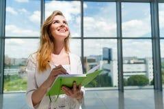 Junge Schönheit, die grünes Notizbuch hält Lizenzfreies Stockbild