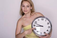 Junge Schönheit, die große Uhr hält Setzen Sie Zeit Konzeptes fest Wenden Sie getrennt auf weißem Hintergrund ein stockbild