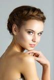 Junge Schönheit, die ihr Gesicht berührt Lizenzfreie Stockbilder