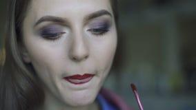 Junge Schönheit, die ihren bordo Lippenstift an einem Spiegel 4K anwendet stock footage