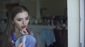 Junge Schönheit, die ihren bordo Lippenstift an einem Spiegel 4K anwendet stock video
